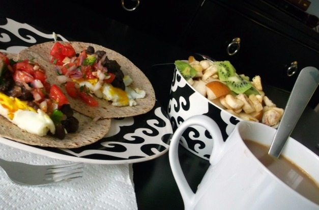 Huevos Rancheros, shown with fruit and coffee